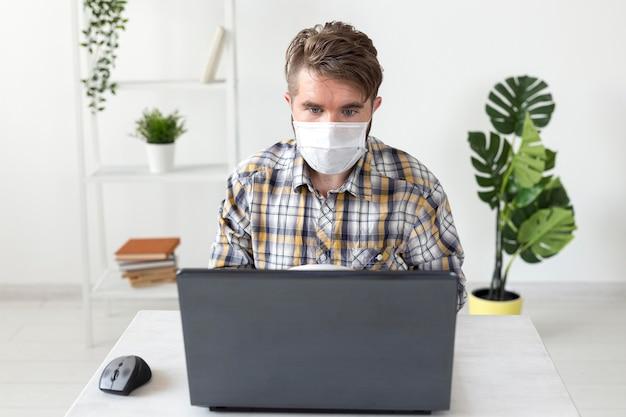 Widok z przodu mężczyzna z maską na twarz pracujący w domu