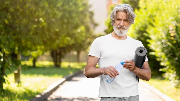 Widok z przodu mężczyzna z matą do jogi i wodą
