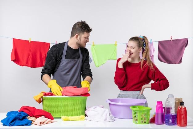 Widok z przodu mężczyzny i jego uśmiechniętej żony stojących za stołowymi koszami na pranie i środkami do prania na stole