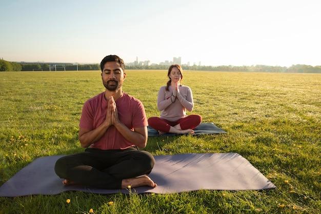 Widok z przodu mężczyzny i kobiety medytujących na zewnątrz na matach do jogi
