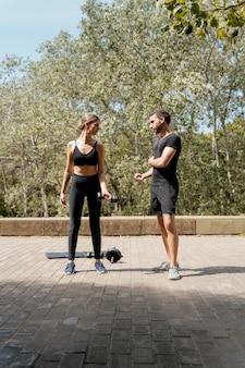 Widok z przodu mężczyzny i kobiety na zewnątrz razem przygotowując się do ćwiczeń