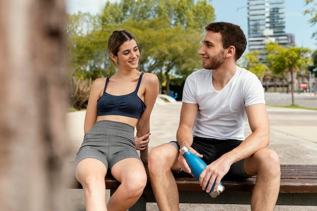 Widok z przodu mężczyzny i kobiety odpoczynku na świeżym powietrzu po ćwiczeniach