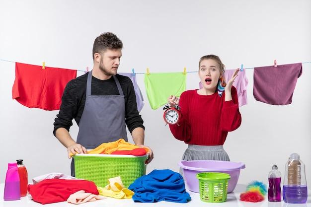 Widok z przodu mężczyzny patrzącego na budzik i jego żonę stojących za stołowymi koszami na pranie i środkami do prania na stole