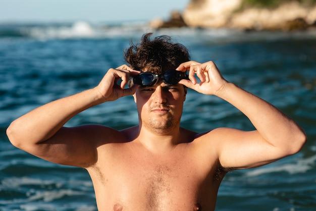 Widok z przodu mężczyzny pływaka zakładającego okulary pływackie
