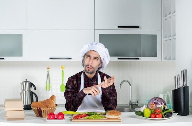 Widok z przodu mężczyzny w zamieszaniu liczącego coś w kuchni