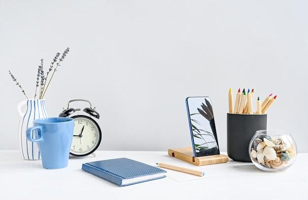 Widok z przodu miejsca pracy z notatnikiem, telefonem, ołówkami, kawą, zegarem na białym stole nad białą ścianą. makieta z miejscem na kopię