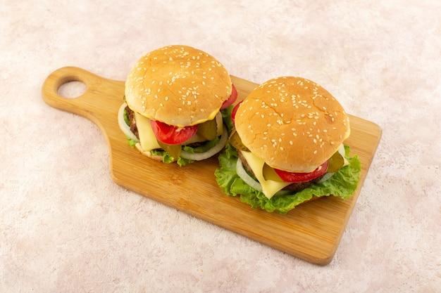 Widok z przodu mięsne hamburgery z warzywami i zieloną sałatą na drewnianym stole