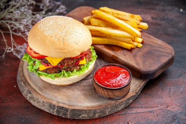 Widok z przodu mięsny burger z pomidorami serowymi i sałatką na ciemnym tle