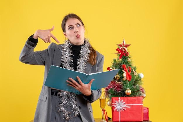 Widok z przodu miło ładna dziewczyna trzyma dokumenty stojące w pobliżu drzewa xmas i koktajl prezenty