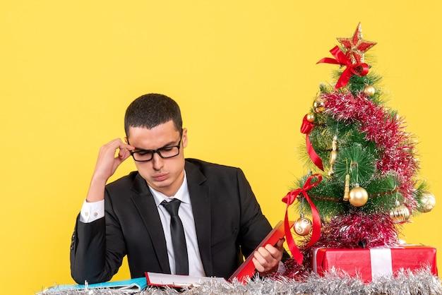 Widok z przodu miło młody człowiek w garniturze siedzi przy stole sprawdzanie dokumentów xmas tree i prezenty