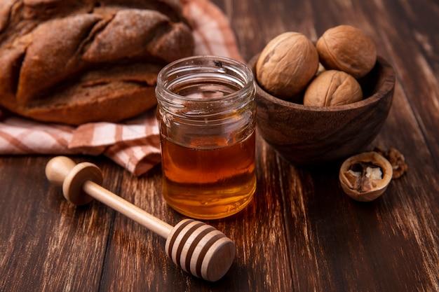 Widok z przodu miód w słoiku z orzechami i bochenkiem czarnego chleba na drewnianym tle