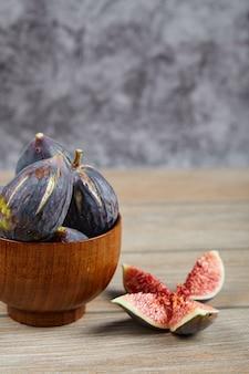 Widok z przodu miski czarnych fig i plasterków fig na drewnianym stole.
