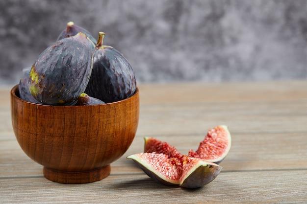 Widok z przodu miski czarnych fig i plastrów fig na drewnianym stole