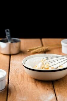 Widok z przodu miski i trzepaczki na drewnianym stole