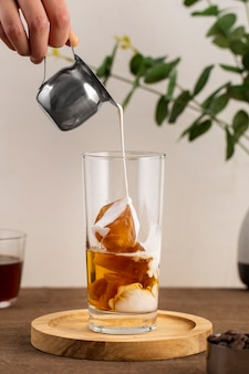 Widok z przodu mleka leje się na mrożoną kawę