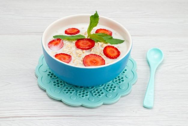 Widok z przodu mleko z płatkami owsianymi wewnątrz talerza z truskawkami na białym, zdrowotne płatki śniadaniowe