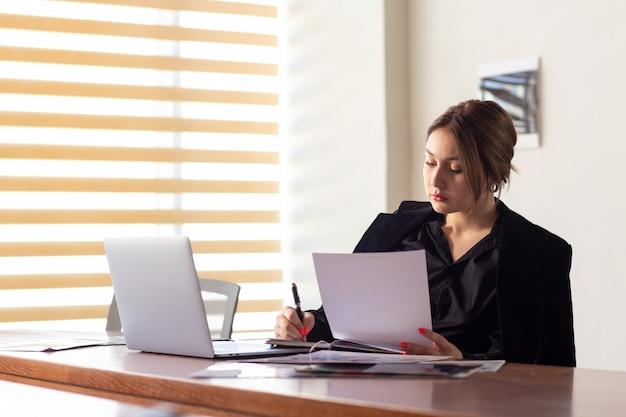 Widok z przodu młoda atrakcyjna bizneswoman w czarnej koszuli czarnej kurtce, używając swojego srebrnego laptopa do czytania, pracując w budynku pracy biurowej
