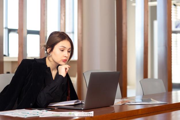 Widok z przodu młoda atrakcyjna bizneswoman w czarnej koszuli czarnej kurtce za pomocą swojego srebrnego laptopa pracującego w budynku pracy biurowej
