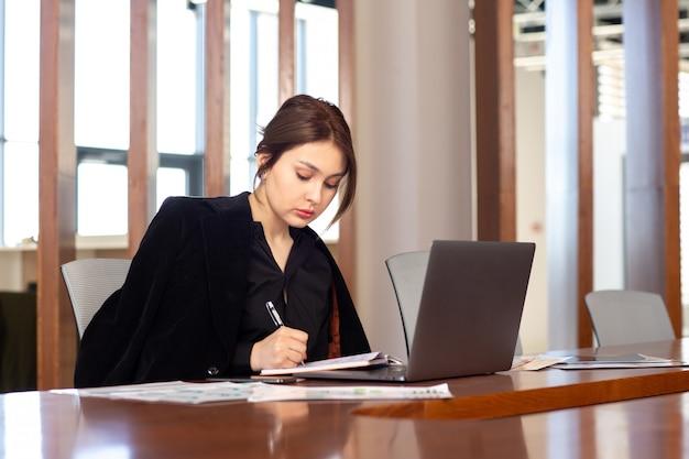 Widok z przodu młoda atrakcyjna bizneswoman w czarnej koszuli czarnej kurtce za pomocą swojego srebrnego laptopa zapisuje notatki pracujące w budynku pracy biurowej