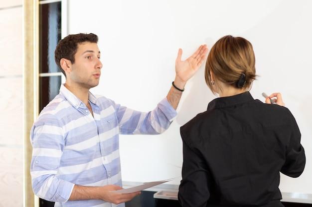 Widok z przodu młoda atrakcyjna bizneswoman w czarnej koszuli wraz z młodym mężczyzną omawiającym grafiki na biurku, podczas gdy młoda dama przedstawia swoją pracę podczas czytania prezentacji pracy w budynku