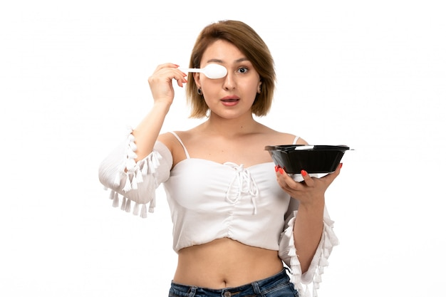 Widok z przodu młoda atrakcyjna dama w białej koszuli i niebieskich dżinsach trzymając czarną miskę jedzenia z niej pozowanie na biały