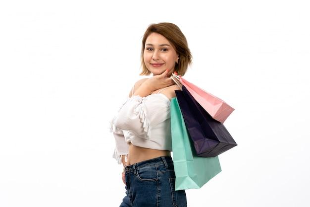 Widok z przodu młoda atrakcyjna dama w białej koszuli i niebieskich dżinsach, trzymając pakiety zakupów, uśmiechając się na białym tle