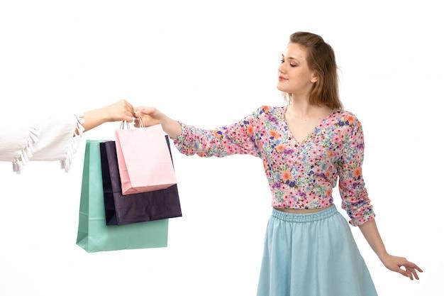 Widok z przodu młoda atrakcyjna dama w koszuli w kolorowe kwiatki i niebieskiej spódnicy dostaje pakiety zakupów na białym tle