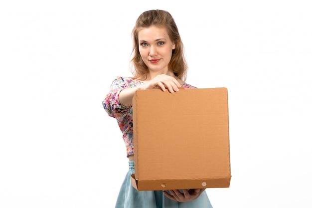 Widok z przodu młoda atrakcyjna dama w koszuli w kolorowe kwiatki i niebieskiej spódnicy, trzymając brązowe pudełko na białym