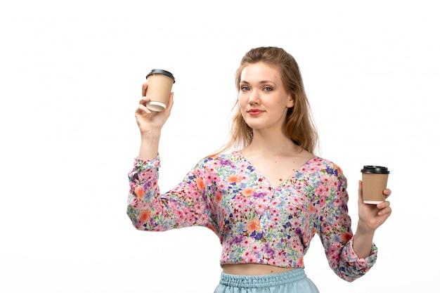 Widok z przodu młoda atrakcyjna dama w koszuli w kolorowe kwiatki i niebieskiej spódnicy, trzymając filiżanki kawy zachwycony, uśmiechając się na białym