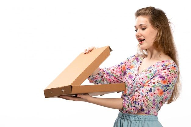 Widok z przodu młoda atrakcyjna dama w koszuli w kolorowe kwiatki i niebieskiej spódnicy z brązowym pudełkiem otwierającym ją na białym tle