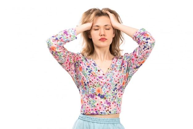 Widok z przodu młoda atrakcyjna dama w koszuli w kolorowe kwiatki i niebieskiej spódnicy z zamkniętymi oczami na białym