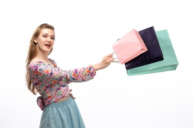 Widok z przodu młoda atrakcyjna dama w koszuli zaprojektowane w kolorowe kwiatki i niebieskiej spódnicy, trzymając pakiety zakupów na białym