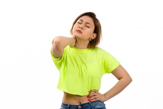 Widok z przodu młoda atrakcyjna dama w zielonej koszuli i niebieskich dżinsach cierpiących na ból szyi na białym