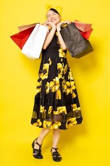 Widok z przodu młoda atrakcyjna dama w żółto-czarnej kwiatowej sukni zaprojektowanej z żółtym bandażem na głowie, pozowanie, trzymając pakiety zakupów na żółtym