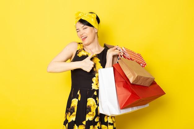 Widok z przodu młoda atrakcyjna dama w żółto-czarnym kwiat zaprojektowanej sukni z żółtym bandażem na głowie uśmiechnięta trzymając pakiety zakupów na żółtym