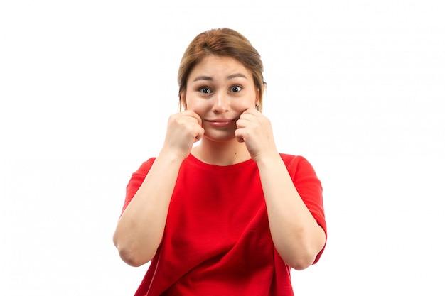 Widok z przodu młoda atrakcyjna dziewczyna w czerwonej koszulce na sobie czarne dżinsy, ciągnąc jej policzki na biało