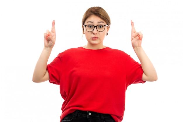 Widok z przodu młoda atrakcyjna dziewczyna w czerwonej koszulce na sobie czarne dżinsy w okularach przeciwsłonecznych, pozowanie na biały