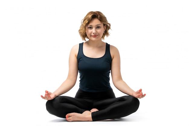 Widok z przodu młoda atrakcyjna dziewczyna w niebieskiej koszuli i czarnych spodniach strój sportowy robi ćwiczenia gimnastyka medytując na białym