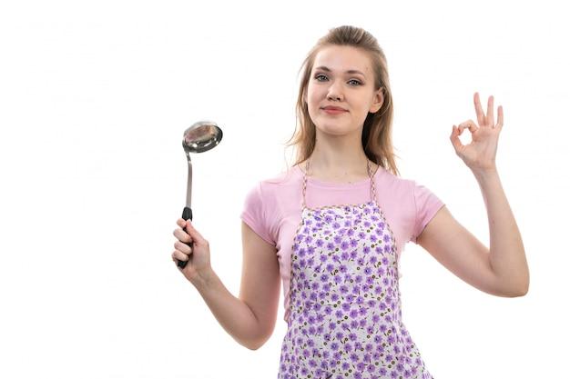 Widok z przodu młoda atrakcyjna gospodyni domowa w różowym koszulowym kolorowym przylądku ono uśmiecha się pozujący trzymający urządzenie na białej tło kuchni kuchni kobiecie