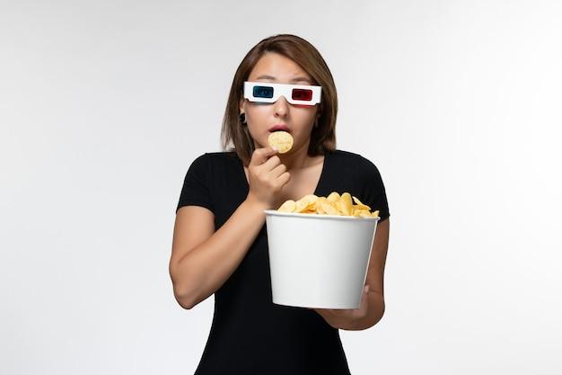 Widok z przodu młoda atrakcyjna kobieta trzyma kipsy ziemniaczane jedzenie d okulary przeciwsłoneczne na białej powierzchni