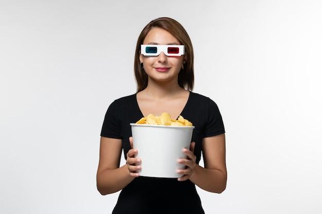 Widok z przodu młoda atrakcyjna kobieta trzyma kosz z cipsami ziemniaczanymi d okulary przeciwsłoneczne na białej powierzchni