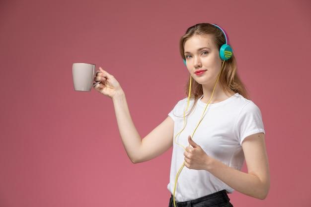 Widok z przodu młoda atrakcyjna kobieta trzyma kubek i słuchanie muzyki na różowej ścianie kolor modelu samica młoda dziewczyna