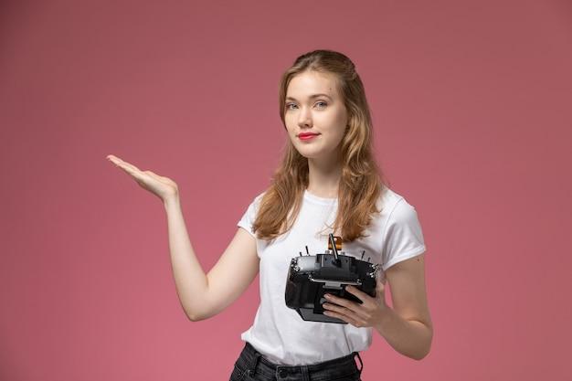 Widok z przodu młoda atrakcyjna kobieta trzyma pilota na różowej ścianie kolor modelu samica młoda dziewczyna