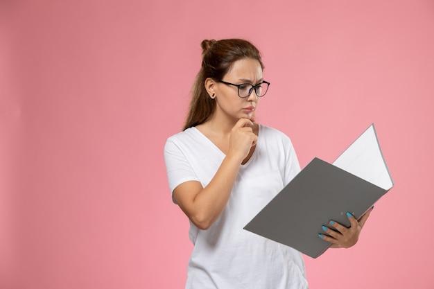 Widok z przodu młoda atrakcyjna kobieta w białej koszulce, czytając szary plik ed na różowym tle