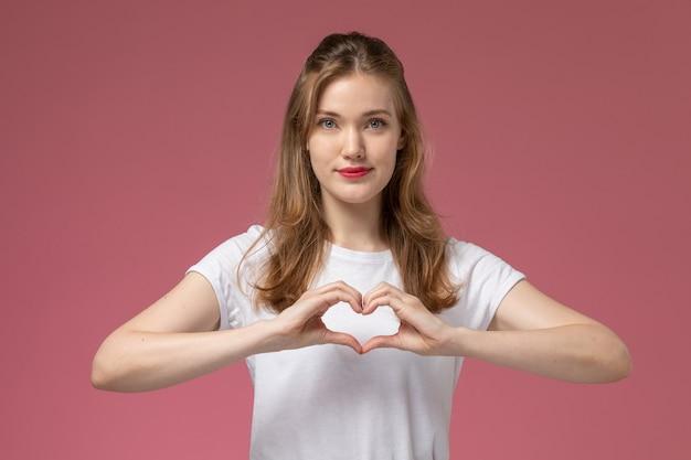 Widok z przodu młoda atrakcyjna kobieta w białej koszulce i czarnych spodniach pozuje pokazując znak serca na różowej ścianie modelka pozuje kolorowe zdjęcie