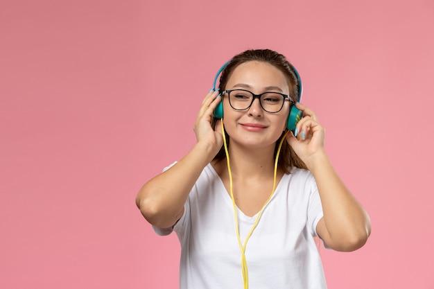 Widok z przodu młoda atrakcyjna kobieta w białej koszulce po prostu pozuje i słucha muzyki przez słuchawki na różowym tle