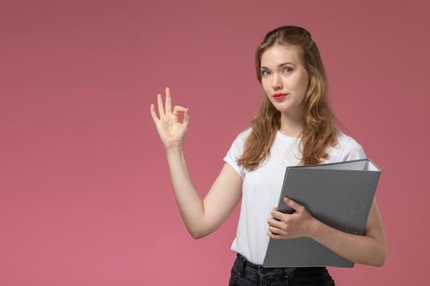 Widok z przodu młoda atrakcyjna kobieta w białej koszulce pokazująca w porządku znak trzymając szary plik na różowej ścianie kolor modelu samica młoda dziewczyna