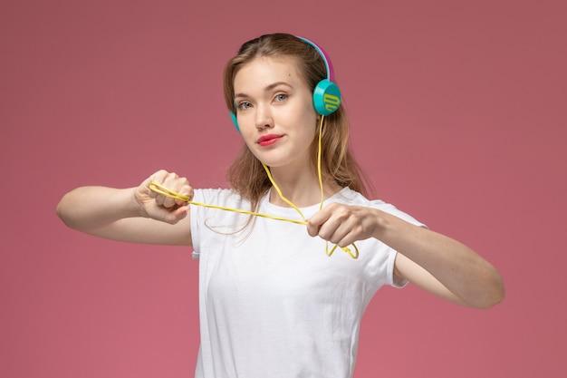 Widok z przodu młoda atrakcyjna kobieta w białej koszulce pozowanie do słuchania muzyki na różowej ścianie kolor modelu samica młoda