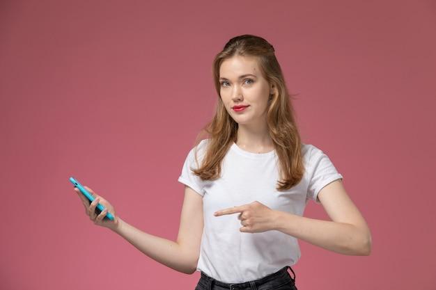 Widok z przodu młoda atrakcyjna kobieta w białej koszulce pozuje trzymając smartfon na różowej ścianie modelka pozuje kolor zdjęcie kobiet młodych