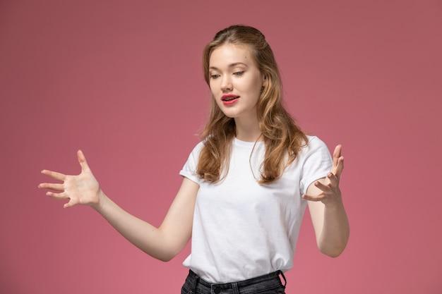 Widok z przodu młoda atrakcyjna kobieta w białej koszulce pozuje z emocjami na różowej ścianie modelka pozuje kolorowe zdjęcie
